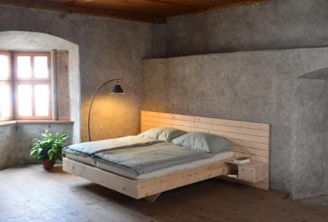 Zirbenbett Osttirol an Betonwand mit Lampe und Fenster